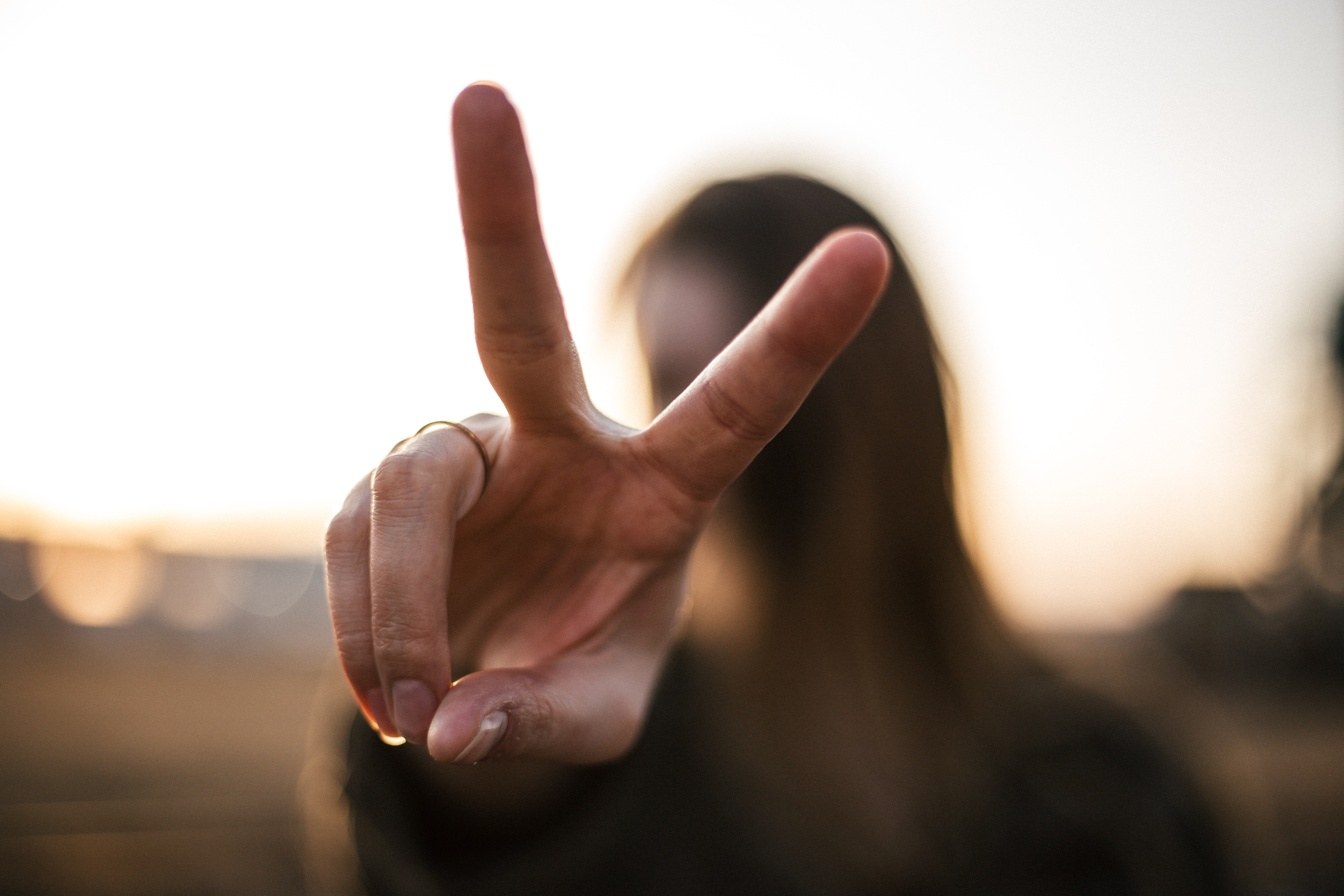 Woman holding up two fingers to signify the two sentences to improve content writing